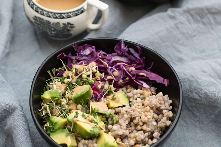 Buckwheat buddha bowl with avocado, red kale and tahini dressing