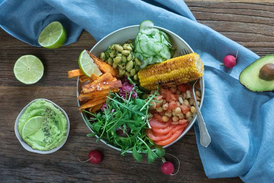 Bowl mit Kichererbsen, Pesto, Süßkartoffel-Pommes und Maiskolben