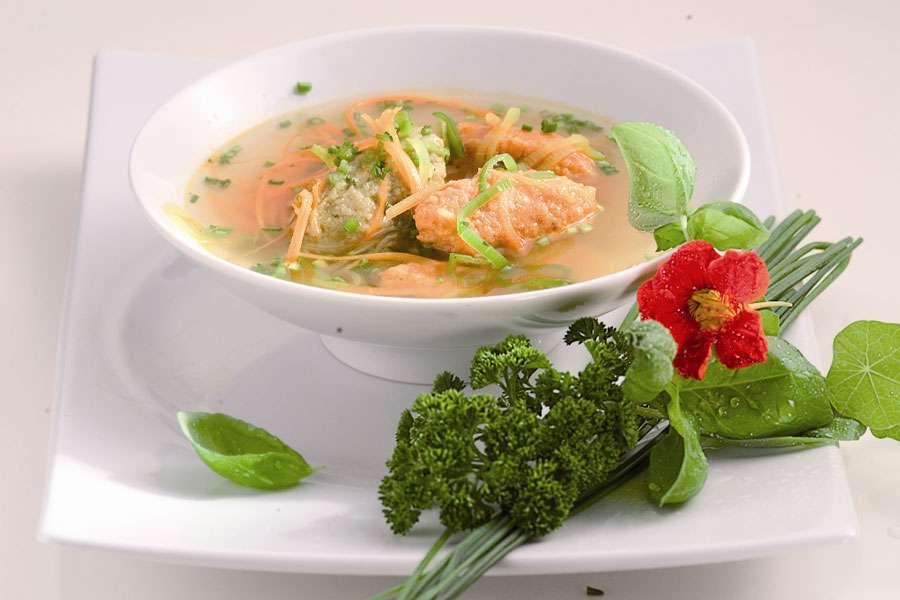 Gemüsesuppe mit roten und grünen Pestonockerl
